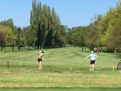 Ellie tees off on the 10th hole, watched by Caz